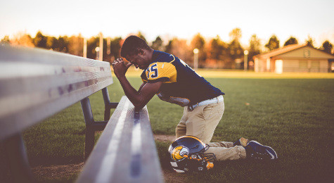 football player praying on his knees