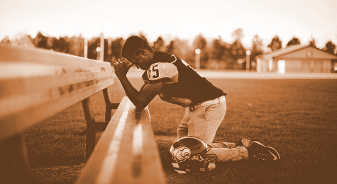 football player kneeling before a wooden bench to pray